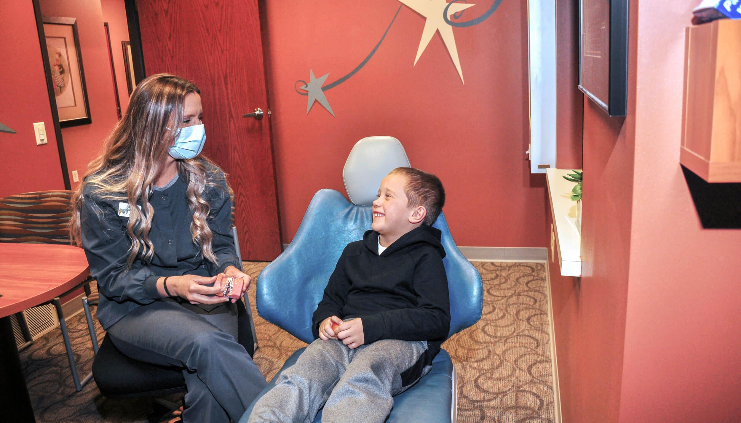 Dental hygienist showing a smiling child a dental mold