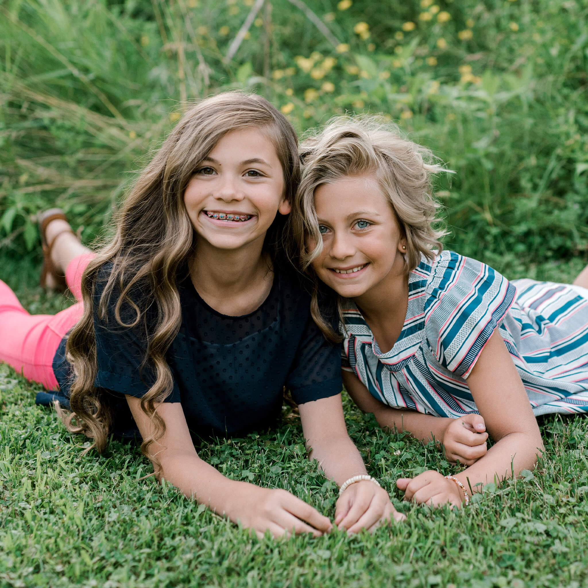 2 girls laying on the grass facing the camera smiling